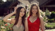 Two gorgeous girls in long gowns and crowns in a garden with roses video