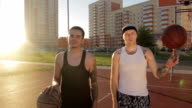 Two guys are on the basketball court in the sun, play with their balls and looking at the camera. video