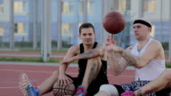 Two guys are sitting on the basketball court with balls and communicate. Spin the ball on his finger. video