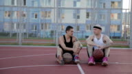 Two guys are sitting on the basketball court with balls and communicate. video