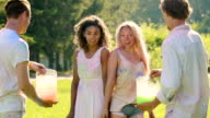 Two guys splashing water at their girlfriends outdoors at Color fest, slowmotion video