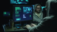 Two hackers in hoods work on a computers with maps and data on display screens in a dark office room. video