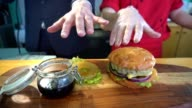 Two hands reaching out for a hamburger video