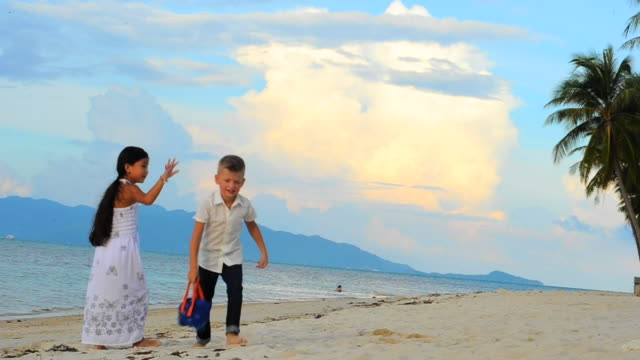 Two handsome kids in casual clothes playing on sandy tropical beach video