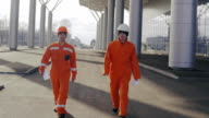 Two happy construction workers walking and jumping together. video
