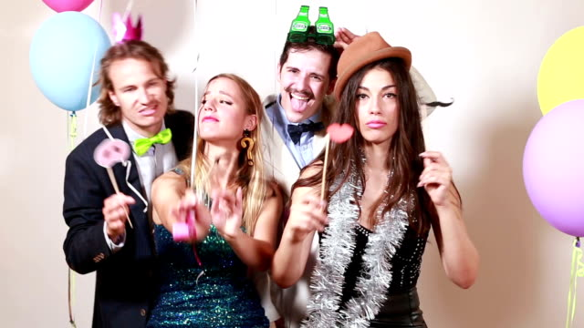 Two happy couples having a great time in photo booth video