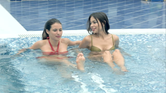 Two happy female freinds enjoying jacuzzi in the swimming pool video