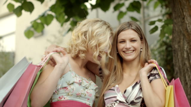 Two happy female friends smiling with shopping bags video