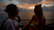 Two happy female travelers talking and laughing at the sunset against a background of the sea. Blonde and brunette are chattering and smiling looking at waving ocean behind them video