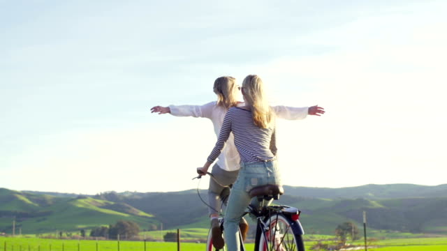 Two Happy Girls Riding Bike With Hands Up In the Air Sunset video