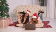 Two happy lady with pc in flat christmas video