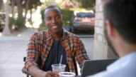 Two happy male friends with cold drinks outside coffee shop video