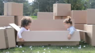 Two happy multicultural babies having fun in cardboard boxes and playing hide and seek video