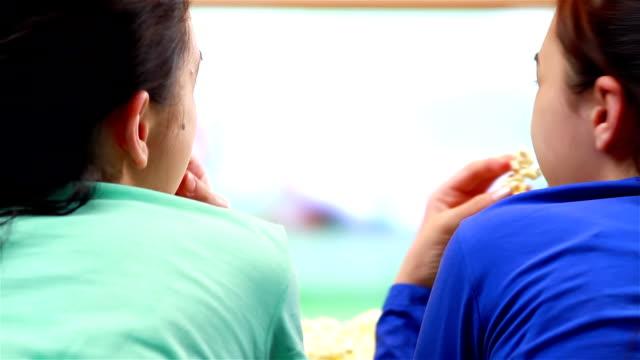 Two happy teenage girls watching tennis sport on smart tv video