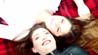 Two happy woman in park smiling on red blanket on sunny autumn day. Two happy beautiful lesbian girls outdoor. video