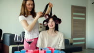 Two happy women friends make fun curler hairstyle each other and have fun at home video