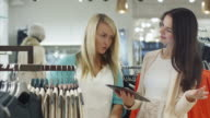 Two happy young girls are shopping clothes and checking a tablet computer in a department store. video