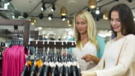 Two happy young girls are shopping clothes in a department store. video