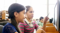 Two Hispanic pre-teen middle school female students are brainstorming ideas in the library of STEM school video