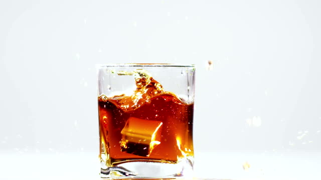 Two ice cubes falling into glass with brandy. Slow motion video