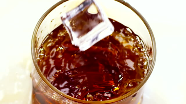 Two ice cubes falling into glass with whiskey. Top view video