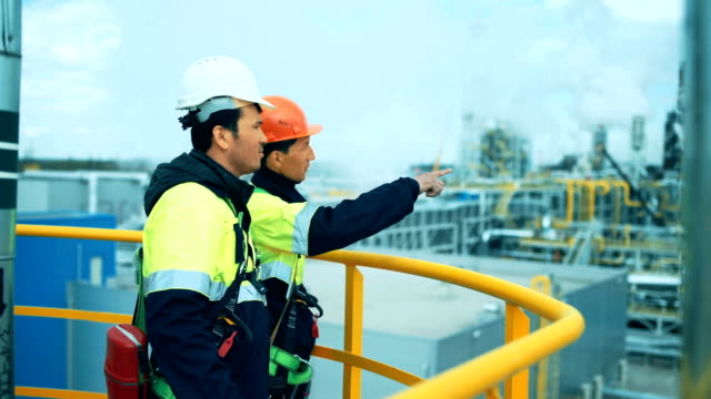 Two industrial workers discussion and pointing for inspection video