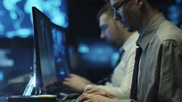 Two IT programmers are working on computer in a dark office room filled with display screens. video