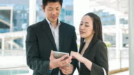 Two Japanese business people working with digital tablet video