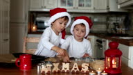 Two kids preparing christmas cookies and put them on baking tray together video