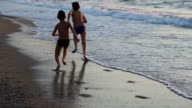 Two kids running on beach in Kusadasi, Turkey video