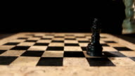 Two kings standing on a chess board, isolated on a black background, the white king overthrows the black king video