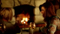 Two laughing and talking friends near fireplace video