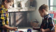 Two little boys painting piggy bank video