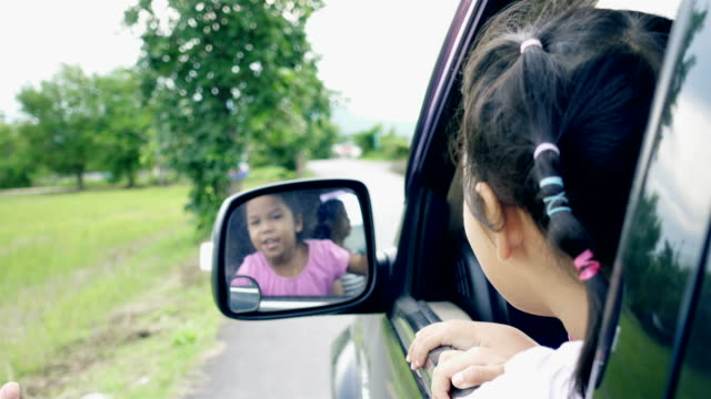 Two little girls are playing on window car together while travel in the countryside video