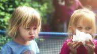 Two Little Girls Eating Hamburger Outside video