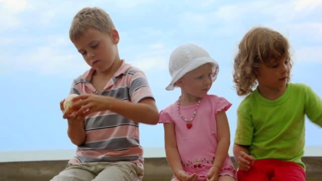 Two little girls sits with boy peeling orange video