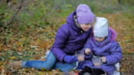 Two little sisters in the autumn park drinking cocoa with marmalade. slow-motion video