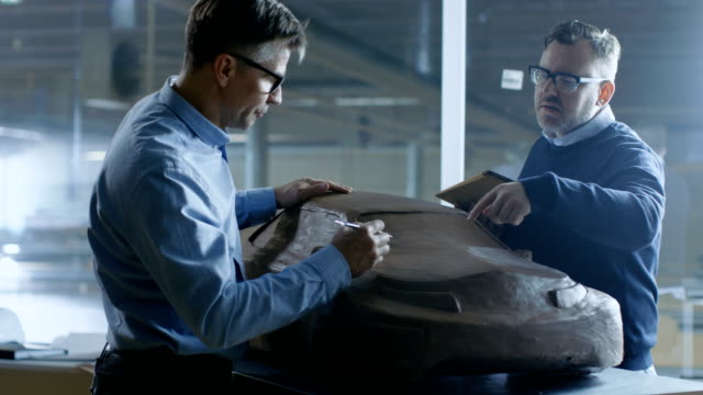 Two Male Automotive Designers Working on a Clay Model of New Generation Electric Car Future Design. One Holds Tablet Computer, Other Sculpts with Clay with Rake/Wire. video