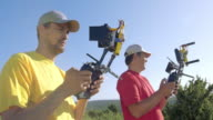 Two male drone operators with remote controllers video