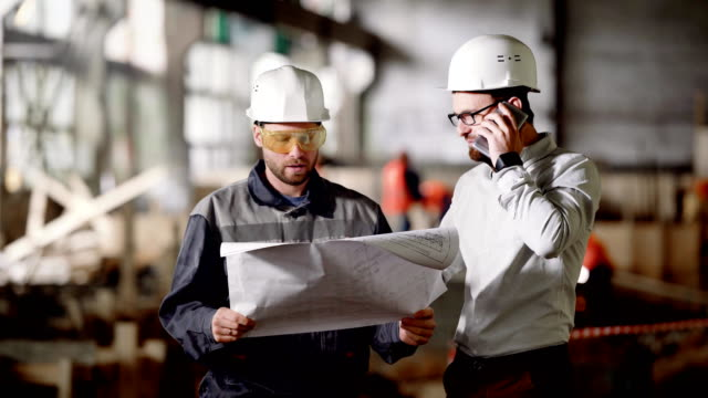 Two male engineers standing in the building site and holding construction plan. Designer speaking on the telephone discussing detailes of project with workman. Foreman listening and holding blueprint video