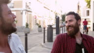 Two male friends talking at a table outside a cafe, Ibiza, shot on R3D video