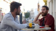 Two male friends talking at a table outside a cafe, Ibiza video