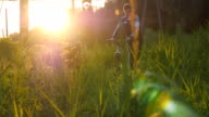 Two male friends walking with their bikes through green grass on the meadow in sunset and talking. video