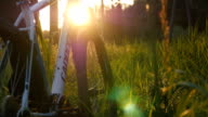 Two male friends walking with their bikes through green grass on the meadow in sunset and talking. Rear back view video