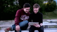 Two male friends with tablet computer talking surfing outdoors video