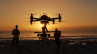 Two male operators controlling drone at sunset video