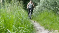 Two man riding a bike on a forest path. Active friends spending their weekend outdoors riding a bike video