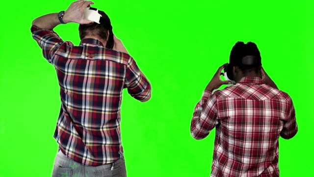 Two man wearing VR googles on green screen video