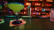 Two Margarita drinks sitting at an indoor bar with cool colors video