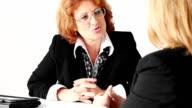 Two mature businesswomen team video